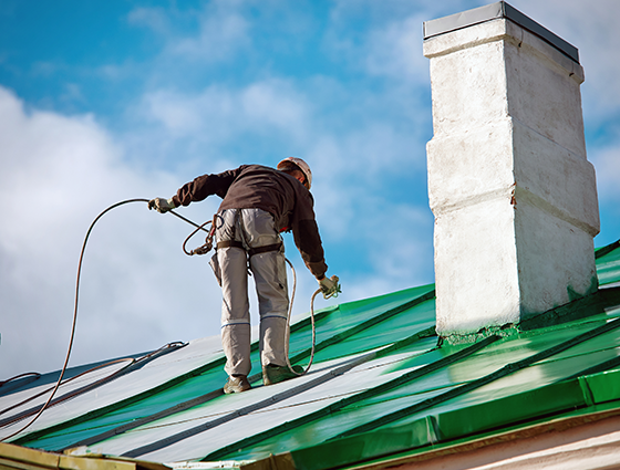 Worker of Industrial Alpinist Services painting roof in green colors with paint spray gun. Professional climber wearing uniform, helmet and using safety harness. Risky job. Extreme occupation.